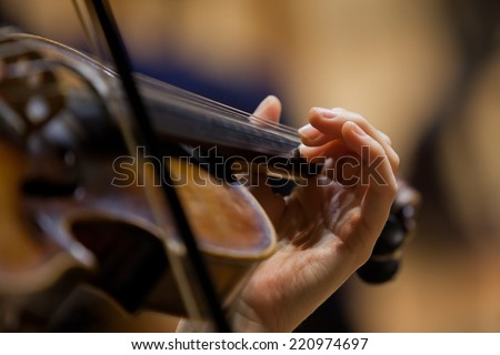 Girl's hand on the strings of a violin - stock photo