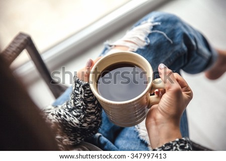 Girl's hands holding a cup of coffee, ripped jeans. Fashion manicur - stock photo