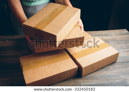 Girl's hands holding the package on the table - stock photo
