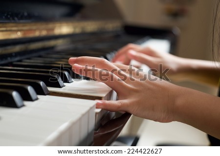 Girl's hands on the keyboard of the piano - stock photo