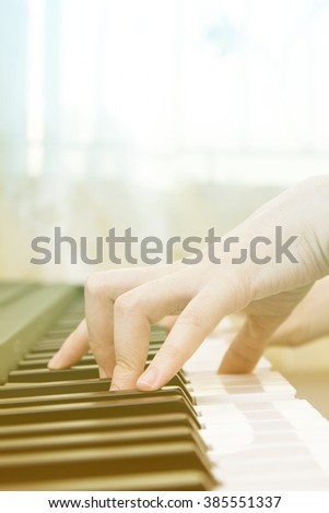 Girl's hands on the keyboard of the piano. Selective focus, shallow depth of field. - stock photo