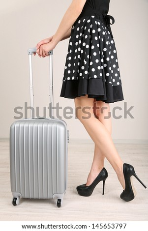 Girl's legs with suitcase in room - stock photo
