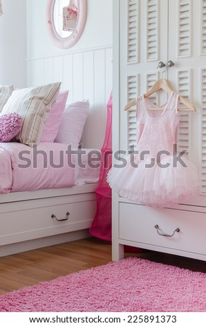 girl's pink dress hanging on wardrobe in bedroom at home - stock photo
