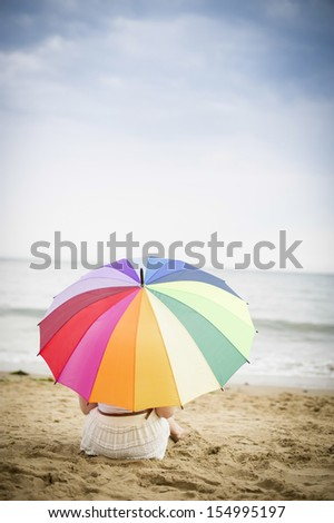 Girl sat under a colourful umbrella on the beach - stock photo