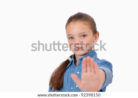 Girl saying stop with her hand against a white background - stock photo