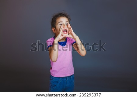 girl screaming away on a gray background - stock photo