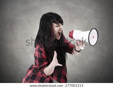 girl screaming with megaphone - stock photo