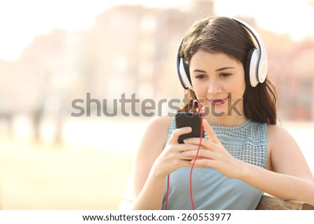Girl searching songs and listening to the music with headphones in an urban park - stock photo