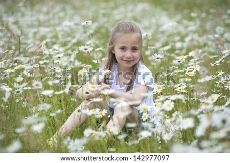 girl seated outdoors in meadow between daisies - stock photo