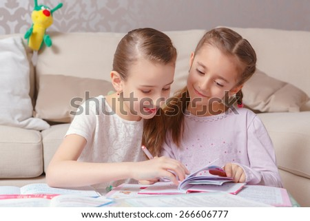 Girl secrets. Two girls in pink drawing with a pen in a note-pad smiling and having fun - stock photo