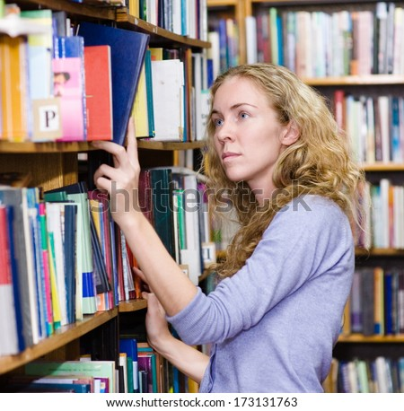 girl selecting book from a bookshelf - stock photo