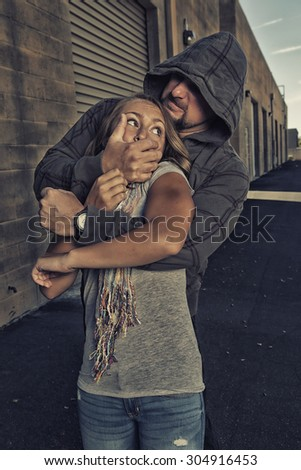 GIRL SELF DEFENSE | A young woman is attacked by a male in an alley. Refuse to be a victim.    - stock photo