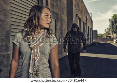 GIRL SELF DEFENSE | A young woman sees a suspicious person walking behind her and plans to defend herself against a male attacker in an alley. Refuse to be a victim.    - stock photo