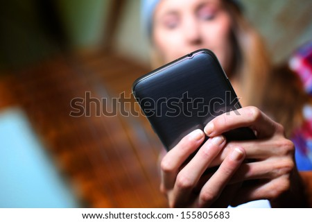 Girl sending message with smartphone - stock photo