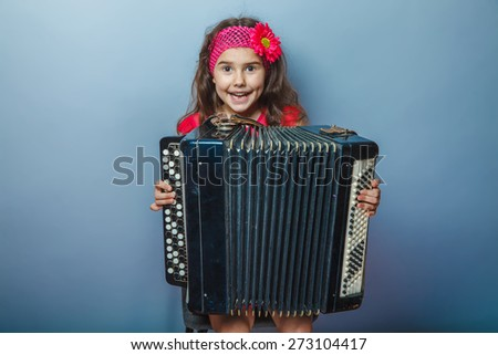 girl seven years of European appearance with a bright-haired child playing on a hairpin akardeone on a gray background, music, happiness - stock photo