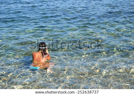girl shooting from behind, with mask diving in crystal clear sea to explore in sunny day - stock photo