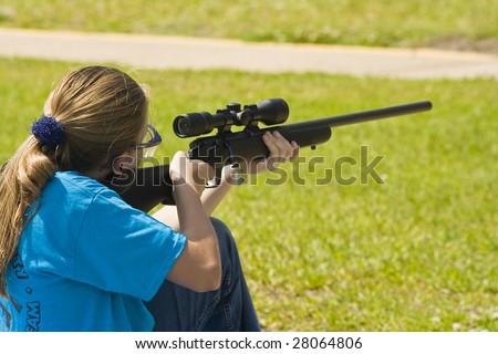 Girl shooting 22 rifle at shooting sports - stock photo