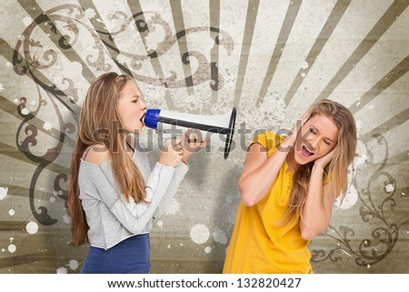 Girl shouting at another through a megaphone on beige art deco style background - stock photo