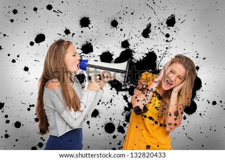 Girl shouting at friend through megaphone on ink splashed background - stock photo