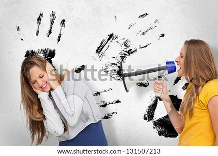 Girl shouting at friend through megaphone on white background with black hand prints - stock photo