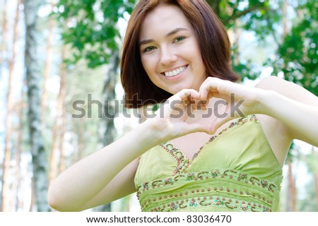 Girl showing a heart sign at the park  (with copy space) - stock photo