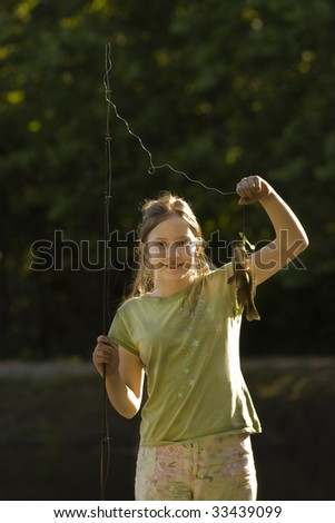 Girl showing off her catch from fishing on dock - stock photo