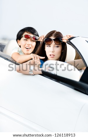 Girl showing something out of the car to her driving friend - stock photo