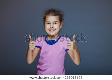 Girl showing thumbs up sign yes on a gray background - stock photo