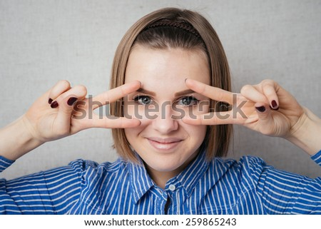 Girl shows two fingers around the eyes - stock photo