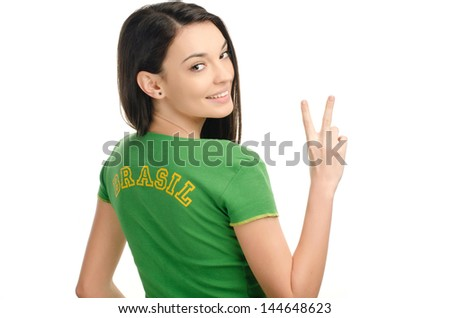 Girl signing victory for Brazil. Attractive girl with Brazil written on her green t-shirt. Isolated on white. - stock photo