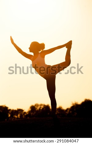 Girl silhouette exercising yoga. Woman in sport suit training in the sunset. - stock photo