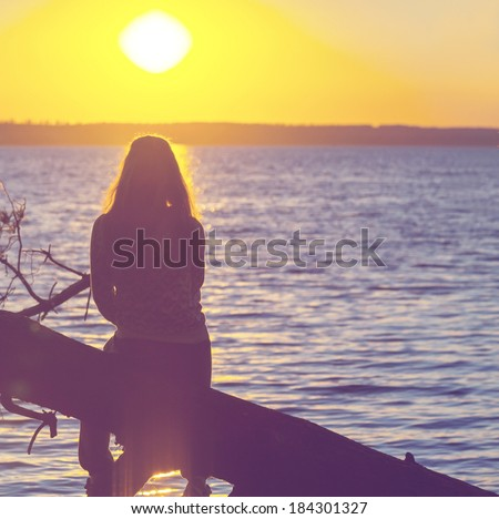 Girl silhouette on the sunset background - stock photo