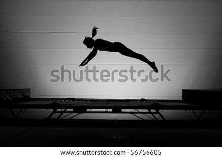 girl silhouette on trampoline - stock photo