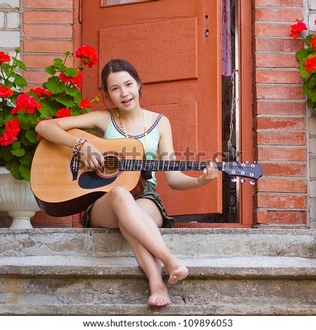 Girl singing and playing the guitar - stock photo