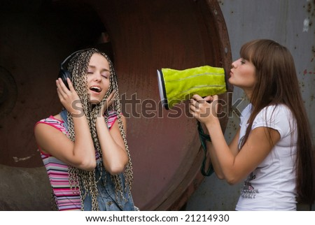 girl singing in megaphone for another girl who listing music in headphones - stock photo
