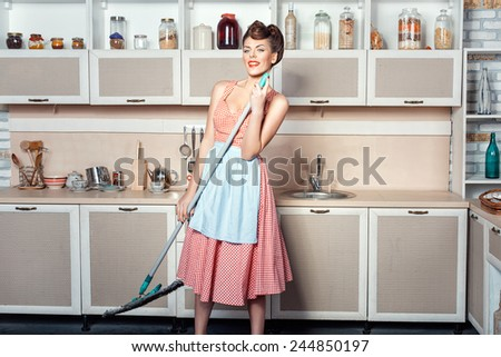 Girl singing in the kitchen, in the hands holding a mop which makes cleaning. - stock photo