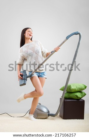 Girl sings while she tidies up the room with the vacuum cleaner - stock photo