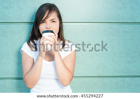 Girl sipping fresh coffee and being dreamy outside on green wall background with copy text area - stock photo