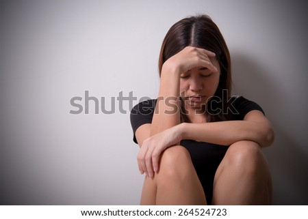 girl sits in a depression on the floor near the wall - stock photo