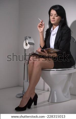 girl sits in toilet and smoking cigarette. businesswoman reading magazine on toilet seat - stock photo