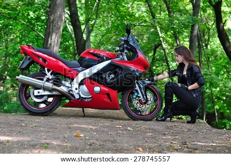 Girl sits near a motorcycle in the woods - stock photo