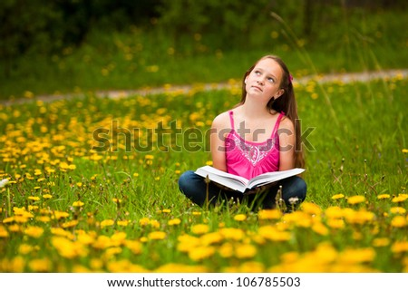 Girl sits on a grass and dreams while reading a book - stock photo