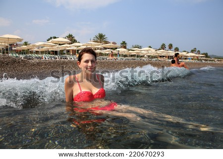 Girl sitting at the pebble the beach at the surf line, on background of sunbeds - stock photo