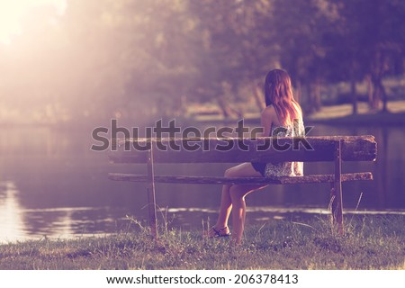 Girl sitting in a bench - stock photo