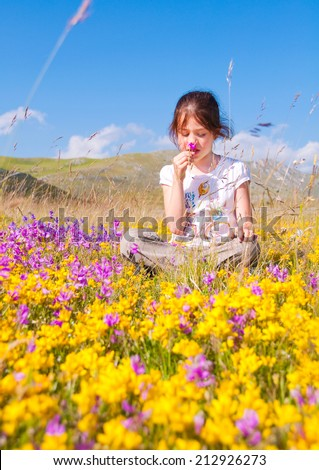 Girl sitting in a flower meadow - stock photo
