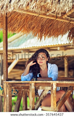 Girl sitting in a seaside cafe on the exotic beach  - stock photo