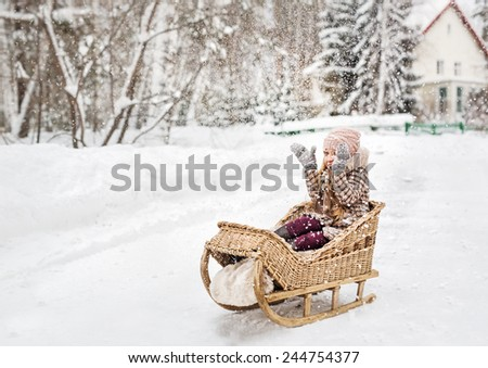 Girl sitting in a vintage wooden sled and happily covering his hands from the falling snow - stock photo