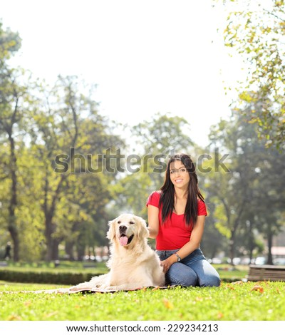 Girl sitting in park with her pet dog shot with tilt and shift lens - stock photo