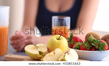 Girl sitting in the kitchen on the desk with fruit and glasses with juice - stock photo
