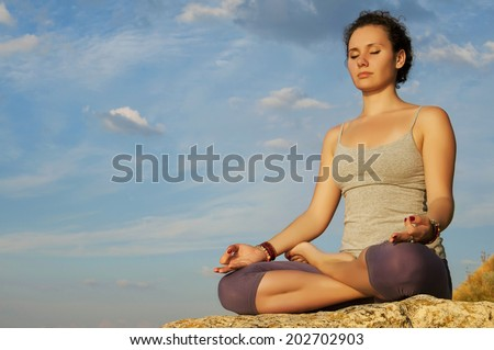 girl sitting in the lotus position on the stone in the warm sunlight. - stock photo